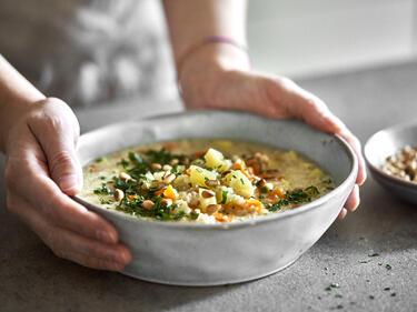 Vegetarische Graupensuppe wird mit Petersilie und Oinienkernen in einer Suppenschüssel serviert