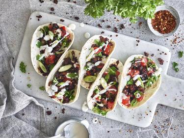 Tofu-Hack serviert in veganen Tacos auf einem Brett