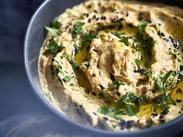 Datteldip mit Olivenöl, Petersilie und Sesam in Schüssel serviert