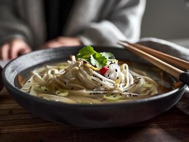 Vegane Pho Bo mit Chai Tee in Schüssel mit Stäbchen serviert
