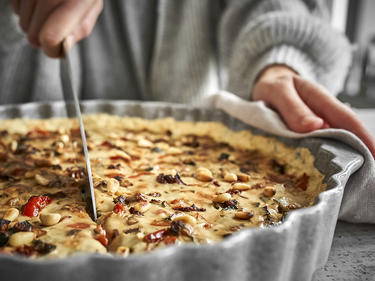 Vegane Quiche mit Ratatouille-Gemüse in Tarteform anschneiden