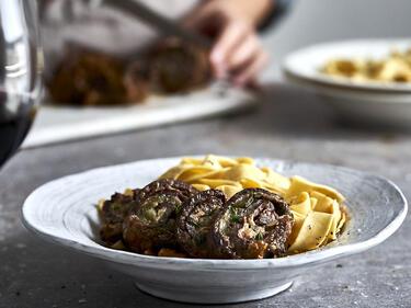 Rouladen im Schnellkochtopf - Das saftige Schmorgericht ist auf einem Teller angerichtet mit einer Portion Bandnudeln.