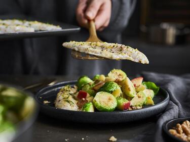Zanderfilet wird mit einem Pfannenwender auf einen Teller mit Rosenkohl-Apfel-Salat gelegt