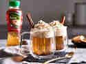 Heißer Bratapfel-Tee mit Sahnehaube, serviert im Glas mit Zimtstange