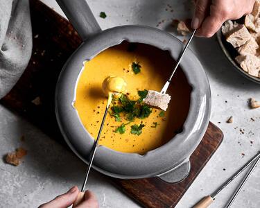Veganes Käsefondue wird mit Brot gedippt!