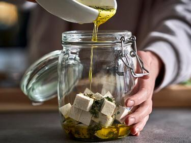 Öl wird in ein Glas über veganen Feta und Kräuter gegossen