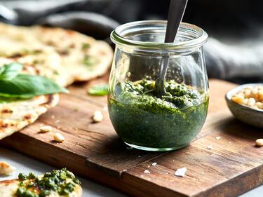 Veganes Pesto mit Basilikum im Glas und mit Brot serviert
