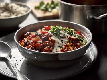 Chili sin Carne vegan mit Sojajoghurt und Koriander in Schüssel serviert