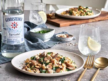 Vegane Pasta mit Mandelsauce auf einem Teller angericht, serviert mit einem Glas Sprudel