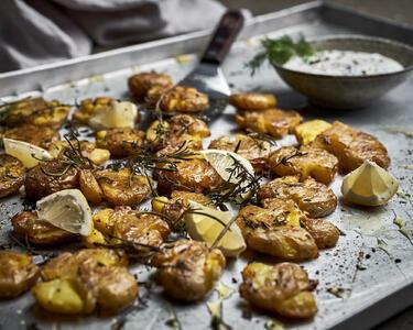 Smashed Potatoes mit Kräuter-Joghurt-Dip auf Backblech serviert