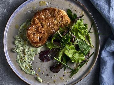Knuspriges Blumenkohl-Schnitzel liegt angerichtet auf einem Teller mit Wildkräutersalat und einer veganen Kräuter-Remoulade