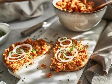 Veganes Mett auf Brot, serviert mit Zwiebelringen und Petersilie