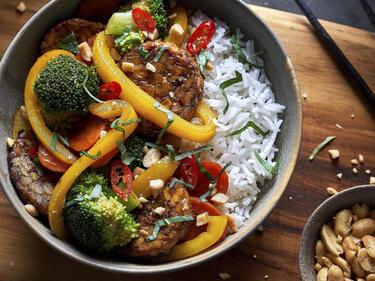 Gebratenes Tempeh mit Gemüse und Reis, serviert in einer Schüssel