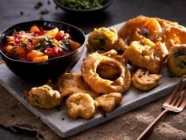 Pakoras auf einem Teller mit Mango-Minze-Chutney im Schälchen dazu