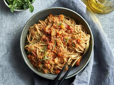 Grünkernbolognese mit Spaghetti, serviert in einer Schüssel