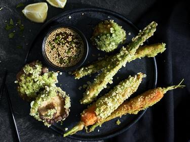 Knuspriges Tempura Gemüse liegt auf einer dunklen Platte serviert. Dazu gibt es einen Asia-Dip mit Sesam.