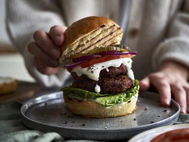 Kidneybohnen-Burger wird auf Teller angerichtet