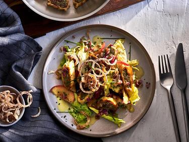 Lauwarmer Maultaschen Salat mit Zwiebeln und Äpfeln auf einem Teller angerichtet, und mit Röstzwiebeln und Walnüsse getoppt