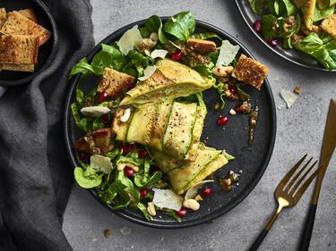 Gebratene Maultaschen mit Salat und Zucchini-Mantel auf einem dunklen Teller serviert