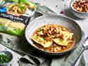 Geschmälzte BÜRGER Maultaschen traditionell schwäbisch in einem tiefen Teller in Brühe serviert und mit Brezel-Speck-Crunch dazu