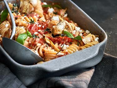 Pasta badet in einer Auflaufform in einer cremigen Sauce aus Feta und Tomaten.