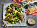 Gebratene Maultaschen im Sesam-Mantel, dazu Brokkoli in Teriyaki-Sauce und Mangowürfel, angerichtet auf einer Betonplatte. Ein Schälchen mit Tahini als Dip daneben.