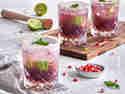 Fruchtig erfrischender Frizz-Mocktail mit Rabenhorst Granatapfel Muttersaft in einem Glas, garniert mit Limetten und Granatapfelkernen