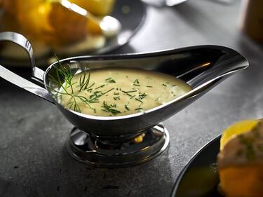 Senf-Dill-Sauce in einer Sauciere mit Kartoffeln auf Teller