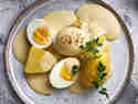 Eier in Senfsauce mit Kartoffeln auf Teller angerichtet