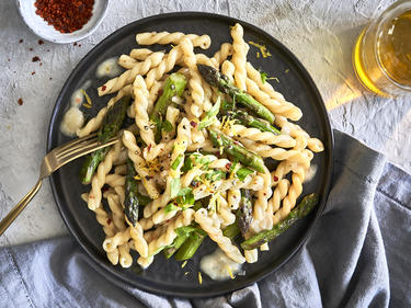 Spargel-Pasta auf Teller mit Gabel serviert