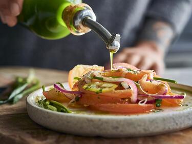 Ein Tomatensalat wird mit grünem Bärlauchöl beträufelt.