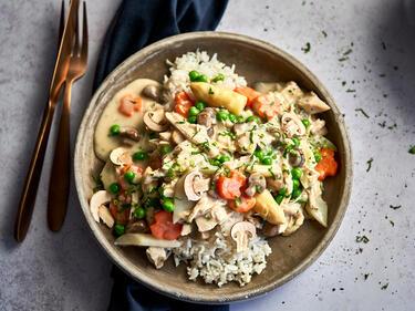 Hühnerfrikassee mit Spargel auf Reis angerichtet und auf einem Teller serviert. Daneben liegen Besteck und Serviette.