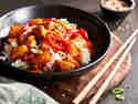 Hähnchen süß-sauer mit Reis in einer Schüssel auf einem Brett serviert.