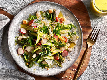 Grüner Spargel-Salat mit Croutons und Parmesanhobeln auf einem Teller angerichtet. Teller steht auf braunem Brett