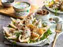 Conchiglioni in cremiger veganer Käsesauce mit Rucola serviert und Walnuss-Kräuter-Karamell getoppt