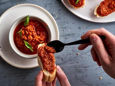 Tomatenpesto mit Löffel auf Brotscheibe gestrichen