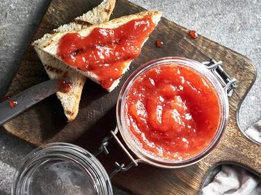 Ein Glas Erdbeermarmelade steht auf einem Brett. Dabei liegen zwei halbe Toasts mit Erdbeermarmelade bestriche.