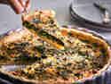 Spinatquiche in einer Tarteform serviert. Ein Stück Spinatquiche wird herausgehoben.