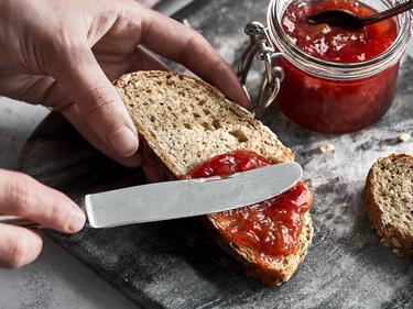 Erdbeer-Rhabarber-Marmelade wird aufs Brot aufgestrichen
