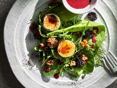 Salat mit Ziegenkäase serviert. Auf dem Salatteller steht ebenfalls das Beerendressing.