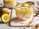Bircher Müsli mit Stückchen der goldenen Kiwi, Kokos und getoppt mit goldene Kiwi-Püree, Kokoschips und gerösteten Haselnüssen