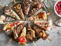 12 Cheesecakestücke am Stiel mit verschiedenen Schokoladen überzogen und bunten Toppings garniert