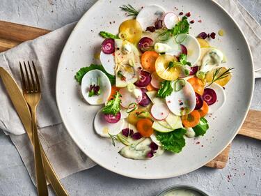 Bunter Mairübe-Salat ist auf einem hellen Teller mit Radieschen und bunten Möhren angerichtet und mit Kresse und Dill-Dressing garniert.