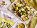Kohlröschen-Salat mit gegrillten Zucchini und Ziegenfrischkäse auf Babyspinat, dazu Honig-Senf-Dressing im Schälchen