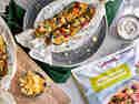 Grill-Zucchini gefüllt mit mexikanischem Gemüse und Cheddar, dazu ein Schälchen Limetten-Schmand und Nachos