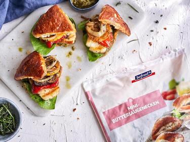 Drei vegetarische Mini-Laugen-Burger auf einem Marmorbrett serviert. Im Anschnitt eine Packung bofrost*Mini-Butterlaugenecken.