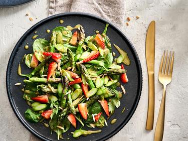 Spargel-Erdbeer-Salat auf einem dunklen Teller serviert. Daneben liegt goldenes Besteck.
