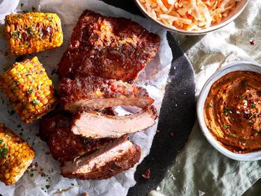 Spare Ribs vom Grill mit Maiskolben und Coleslaw serviert