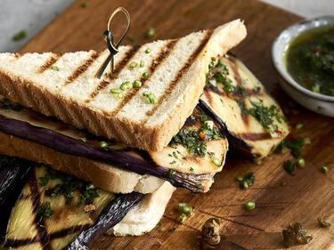 Gegrillte Auberginen in einem Sandwich gespapelt. Das Sandwich liegt halbiert auf einem Brettchen.