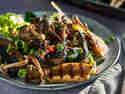 Gegrillte Pilze mit Salat vermengt und in einer Schale serviert.